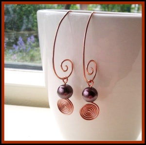 Wire wrapped copper spiral earrings by Laurelinde Sieraden