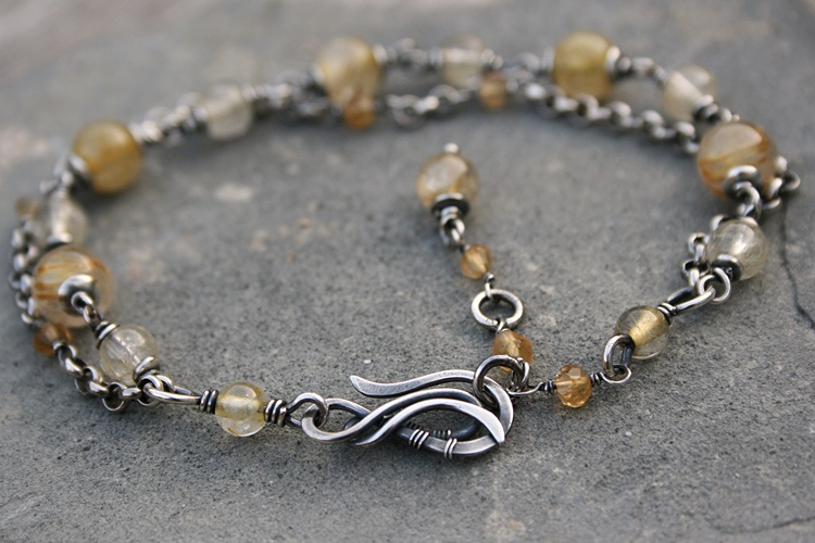 Maeve, made by Yeske. A bracelet with round rutilated quartz beads of various sizes and shades of yellow, and small facetted citrine beads. With handcrafted clasp that can be fastened at three different lengths. Oxidized, sanded and tumbler-polished for shiny finish.