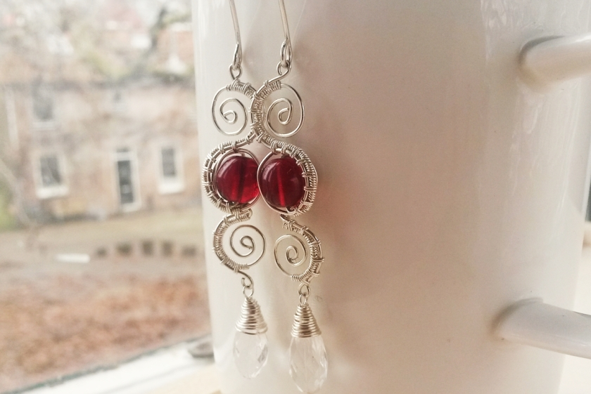 zilveren oorbellen met gewoven textuur, fijne spiralen en granaatrode glaskralen
