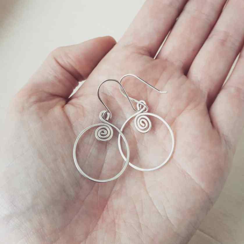 Zilveren spiraal oorbellen op hand